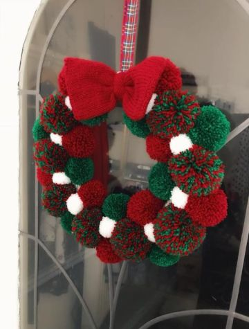 2-07-a-christmas-pompom-wreath-of-white-green-and-red-pompoms-and-a-knit-bow