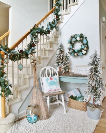 29-coastal-christmas-entryway-decor-in-pale-blue-with-a-garland-a-wreath-some-trees-and-ornaments