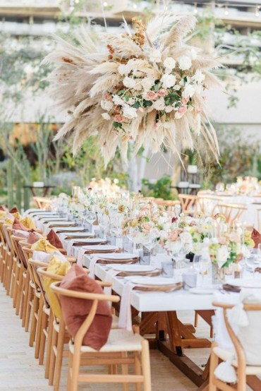 A-bright-and-chic-spring-wedding-reception-with-bright-blooms-greenery-a-lush-chandelier-of-pampas-grass-and-blush-flowers