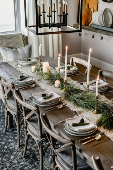 A-chic-rustic-christmas-table-with-a-burlap-runner-porcelain-plates-tall-candles-and-an-evergreen-runner