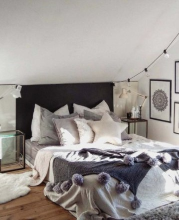 A-faux-fur-rug-a-knit-blanket-with-large-pompoms-and-some-fur-pillows-and-lights-make-the-bedroom-winter-ready
