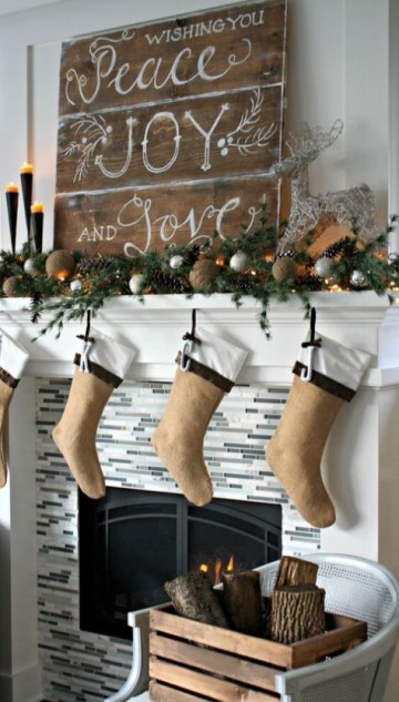 A-large-wooden-plank-christmas-sign-an-evergreen-garland-with-vine-balls-pinecones-and-stockings-of-felt