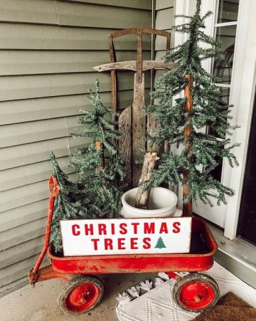 A-red-cart-with-a-sign-three-christmas-trees-in-buckets-is-a-nice-rustic-porch-decoration