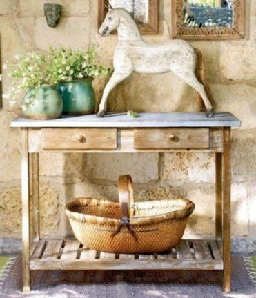 02-a-rustic-console-table-with-a-large-basket-a-statuette-and-some-potted-flowers