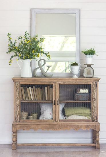 1-04-a-vintage-console-with-some-greenery-in-a-jug-a-pot-and-a-moss-ball