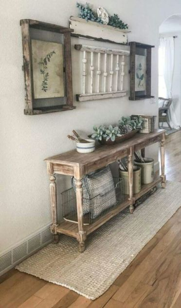 1-a-vintage-meets-farmhouse-entryway-with-a-wooden-console-vintage-posters-as-artworks-and-some-jute-integrated