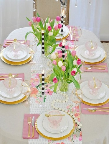 A-colorful-spring-table-setting-with-pink-napkins-a-floral-table-runner-wooden-beads-and-striped-candles-plus-pink-glass