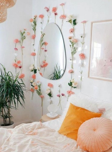 Faux-pink-blooms-attached-to-the-wall-and-a-marigold-and-peachy-pillow-make-the-bedroom-spring-like