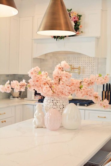Fresh-pink-blooming-branches-in-a-vase-and-a-matching-pink-wreath-make-the-space-look-spring-like