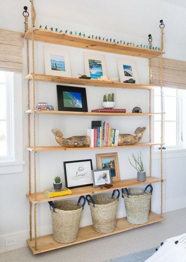2-24-an-oversized-hanging-shelving-unit-with-ropes-and-shelves-going-down-to-the-floor-and-baskets-on-the-lowest-piece