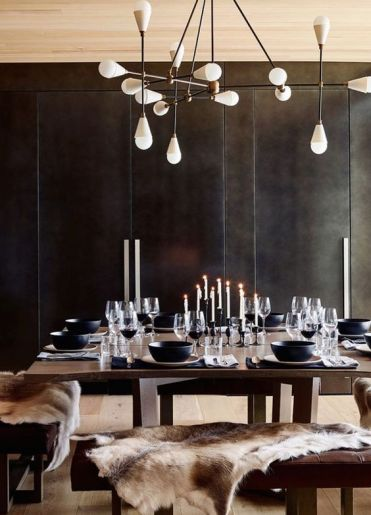A-moody-modern-chalet-dining-space-with-black-walls-dark-modenr-furniture-a-catchy-chandelier-and-candles