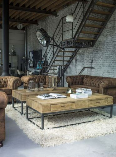 An-industrial-living-room-with-whitewashed-brick-walls-leather-tufted-sofas-wood-and-metal-coffee-tables