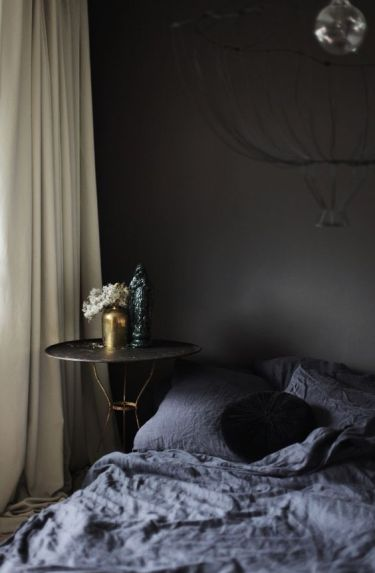 Black-walls-graphite-bedding-and-a-refined-nightstand-with-gold-legs