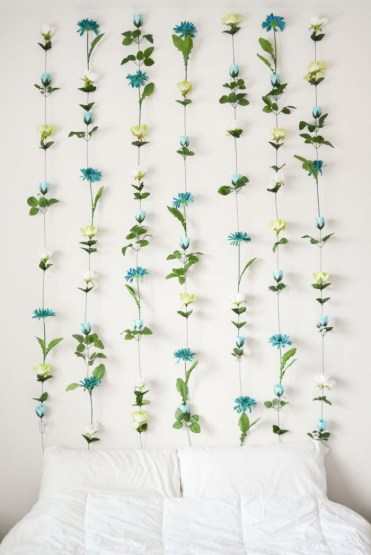 Handmade-faux-flower-wall-decoration-in-green-cream-and-teal-mounted-on-a-white-wall-near-a-bed-diys-for-girls