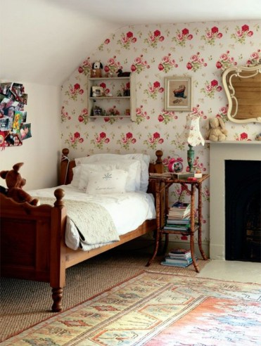 Vintage-style-wooden-bed-with-white-duvet-and-pillows-in-a-room-with-an-ornamental-rug-and-a-fireplace-teenage-girl-room-ideas-floral-wallpaper-on-one-wall