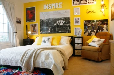 Yellow-wall-with-posters-and-framed-images-in-a-room-with-a-brown-armchair-a-large-bed-and-a-window-with-white-curtains-cool-beds-for-teens