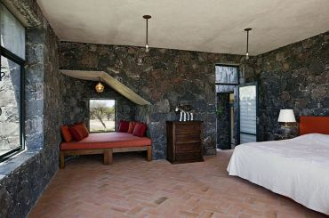 1-mediterranean-bedroom-showcases-terracotta-tiles-and-dark-stone-walls