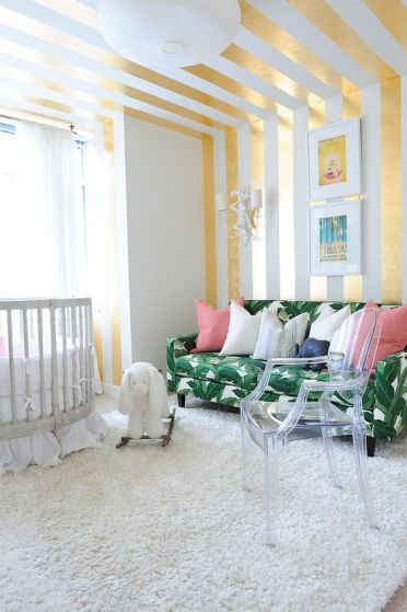 3-12-a-bright-nursery-with-a-glam-feel-a-striped-gold-and-white-wall-and-ceiling-a-tropical-leaf-print-sofa-and-an-acrylic-chair