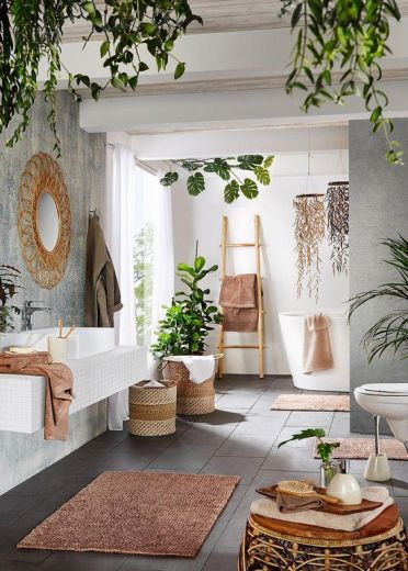 A-contemporary-meets-boho-space-with-potted-greenery-baskets-rattan-furniture-a-wicker-mirror-and-a-ladder