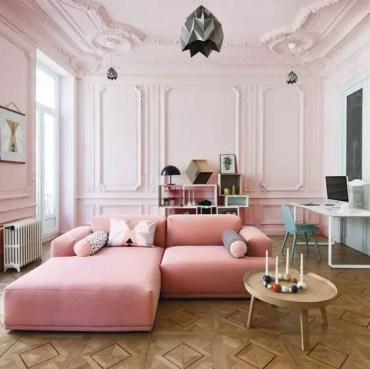 Un-splendido-soggiorno-blush-con-modanatura-un-divano-rosa-un-contenitore-creativo-e-uno-spazio-di-lavoro-a-parete