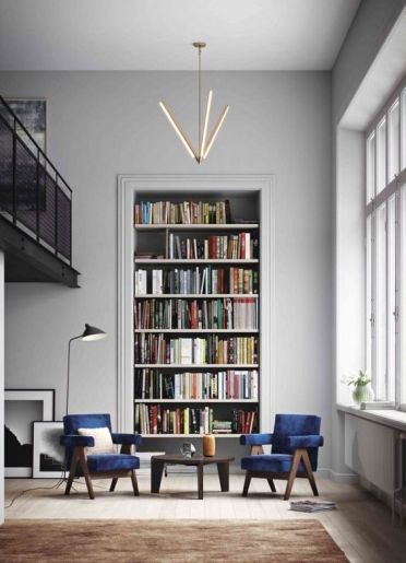 A-stylish-conversation-and-reading-nook-with-navy-velvet-chairs-a-large-built-in-bookshelf-unit-and-a-cool-chandelier-3