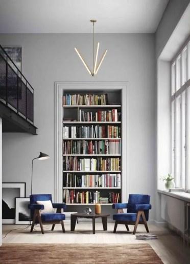 Un-elegante-angolo-conversazione-e-lettura-con-sedie-di-velluto-blu-scuro-una-grande-libreria-incorporata-e-un-bellissimo-lampadario-3