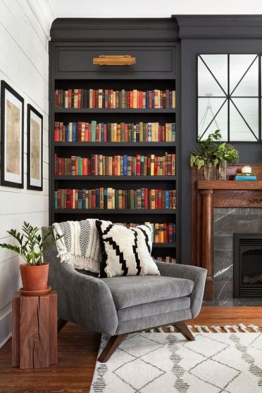 A-stylish-moody-space-with-dark-built-in-bookshelves-a-marble-fireplace-and-a-grey-chair-for-much-comfort-3