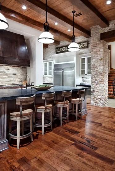 04-una-cucina-rustica-con-pavimento-in-legno-dai-colori-ricchi-e-sedie-in-legno-vintage-imbiancate