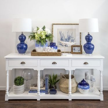 112-a-white-vintage-console-with-bold-blue-lamps-and-vases-plants-in-pots-baskets-and-corals