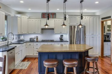 Cabinets-draped-in-white-enamel-coupled-with-bright-blue-island-in-the-kitchen