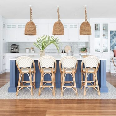 A-beach-kitchen-with-white-cabinetry-a-navy-kitchen-island-rattan-chairs-woven-lamps-and-greenery-775x775-1