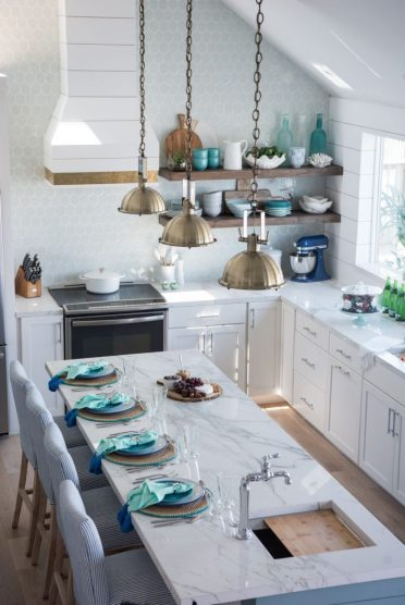 A-charming-coastal-kitchen-with-white-cabients-an-aqua-scale-tile-backsplash-a-marble-kitchen-island-and-blue-striped-chairs-775x1161-1