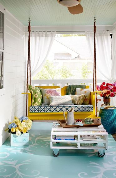 1-a-colroful-front-porch-with-a-yellow-hanging-bench-printed-pillows-a-pallet-coffee-table-and-some-blooms