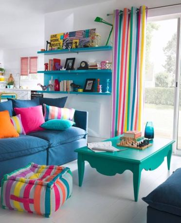 A-bright-living-room-with-striped-curtains-a-matching-ottoman-colorful-pillows-and-some-bold-furniture-for-fun