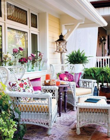 A-colorful-summer-porhc-with-white-wicker-furniture-a-purple-table-lots-of-greenery-printed-pillows-and-potted-greenery
