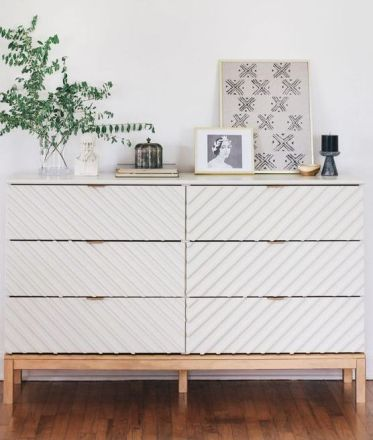 A-trendy-tarva-dresser-hack-with-striped-wall-panels-light-colored-stained-legs-and-a-frame-and-brass-pulls