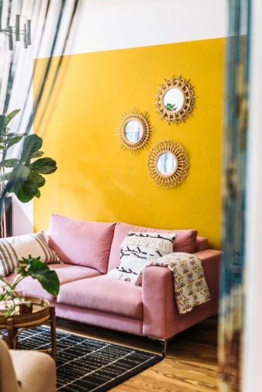 A-colorful-boho-living-room-with-a-sunny-yellow-accent-wall-a-pink-sofa-a-gallery-wall-of-mirrors-and-potted-greenery