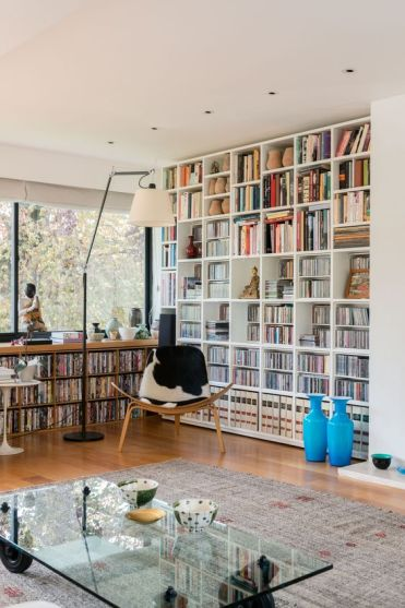 A-modern-home-library-with-a-large-bookcase-and-a-built-in-window-unit-plus-a-cowhide-chair
