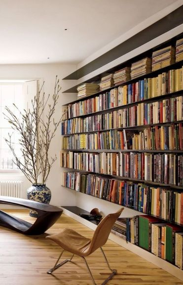 A-modern-refined-home-library-with-an-oversized-floating-bookshelf-unit-a-dark-wooden-table-and-a-leather-chair