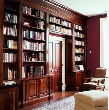 1-french-walnut-shelves-around-the-doorway-along-with-red-walls-shape-a-classic-reading-room