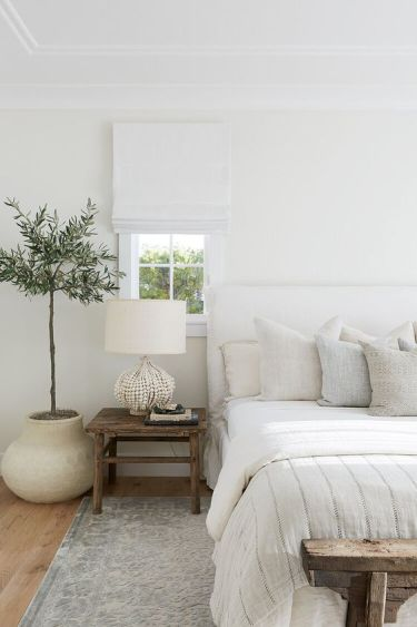 1-a-neutral-bedroom-with-a-white-upholstered-bed-neutral-pillows-a-white-lamp-and-white-shades-plus-a-statement-plant