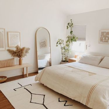 1-a-neutral-boho-bedroom-with-a-bed-a-wooden-bench-a-curved-mirror-potted-plants-and-artworks