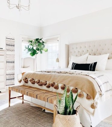 1-a-neutral-boho-bedroom-with-a-creamy-bed-a-woven-bench-boho-hangings-statement-plants-and-tassel-blankets