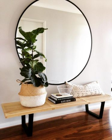 Large-round-mirror-above-a-wood-bench