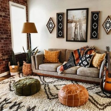 A-boho-living-room-with-folksy-artworks-and-pillows-leather-and-velvet-ottomans-potted-plants-and-a-comfy-sofa