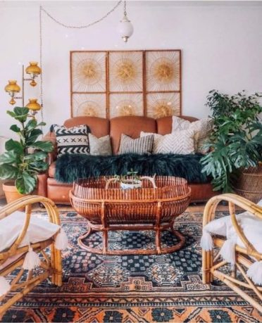 A-bright-moroccan-living-room-with-a-rust-leather-sofa-rattan-chairs-potted-plants-and-moroccan-lamps