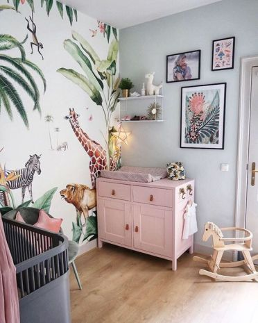 A-bright-tropical-nursery-with-a-pink-changing-table-a-bright-jungle-print-wall-bright-artworks-and-a-grey-crib-with-a-pink-canopy