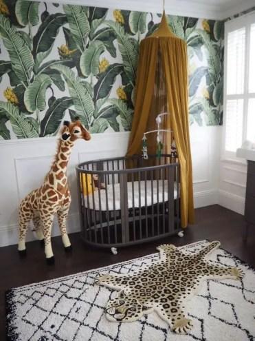 A-jungle-nursery-with-a-tropical-leaf-wall-a-dark-crib-a-mustard-canopy-a-fun-rug-and-a-toy-giraffe