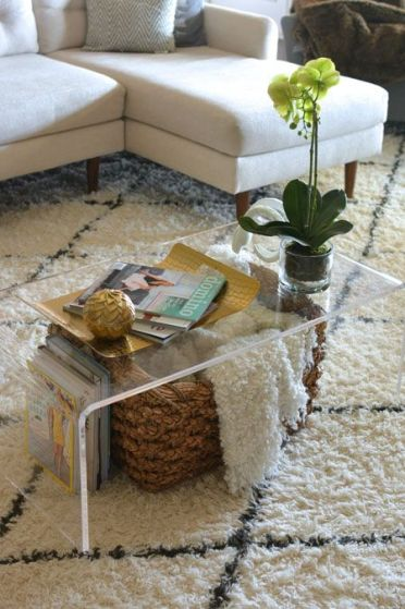 An-acrylic-coffee-table-with-a-basket-for-storage-and-some-books-under-the-top-is-a-cool-idea