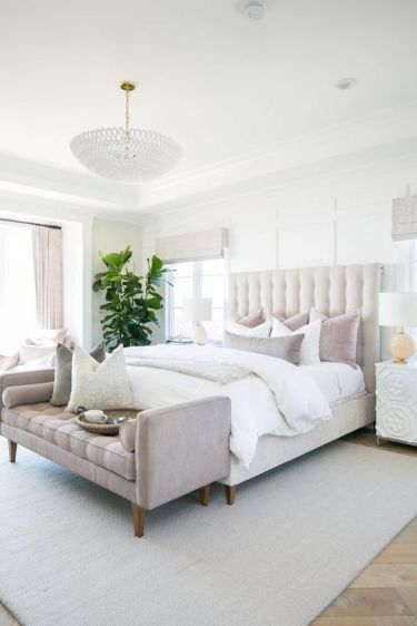An-elegant-neutral-bedroom-with-a-creamy-bed-neutral-and-pastel-bedding-a-pastel-bench-and-a-statement-plant